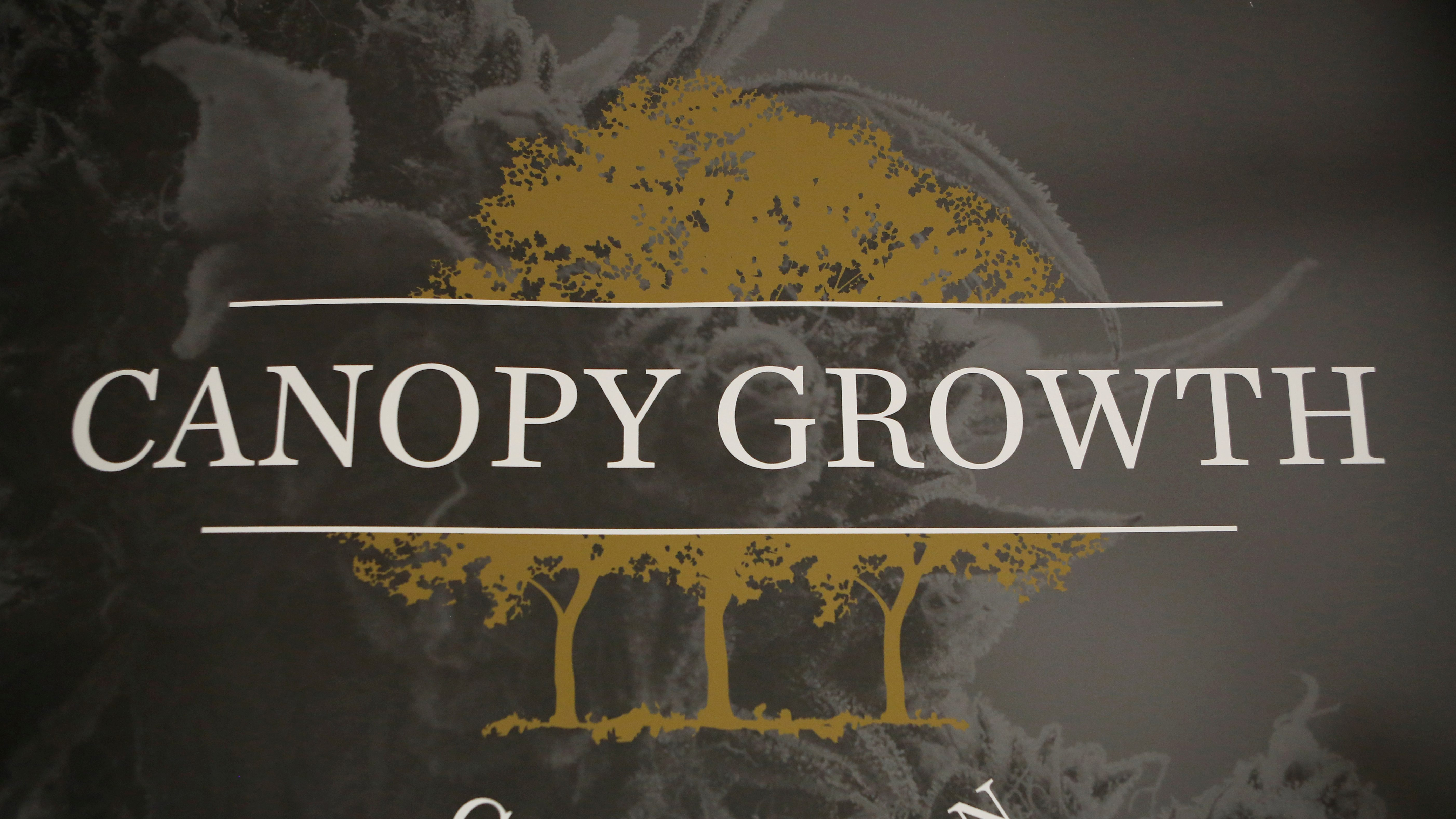 A closeup photograph of Canopy Growth Corporation's logo, white all-caps san serif letters in front of three light brown trees.