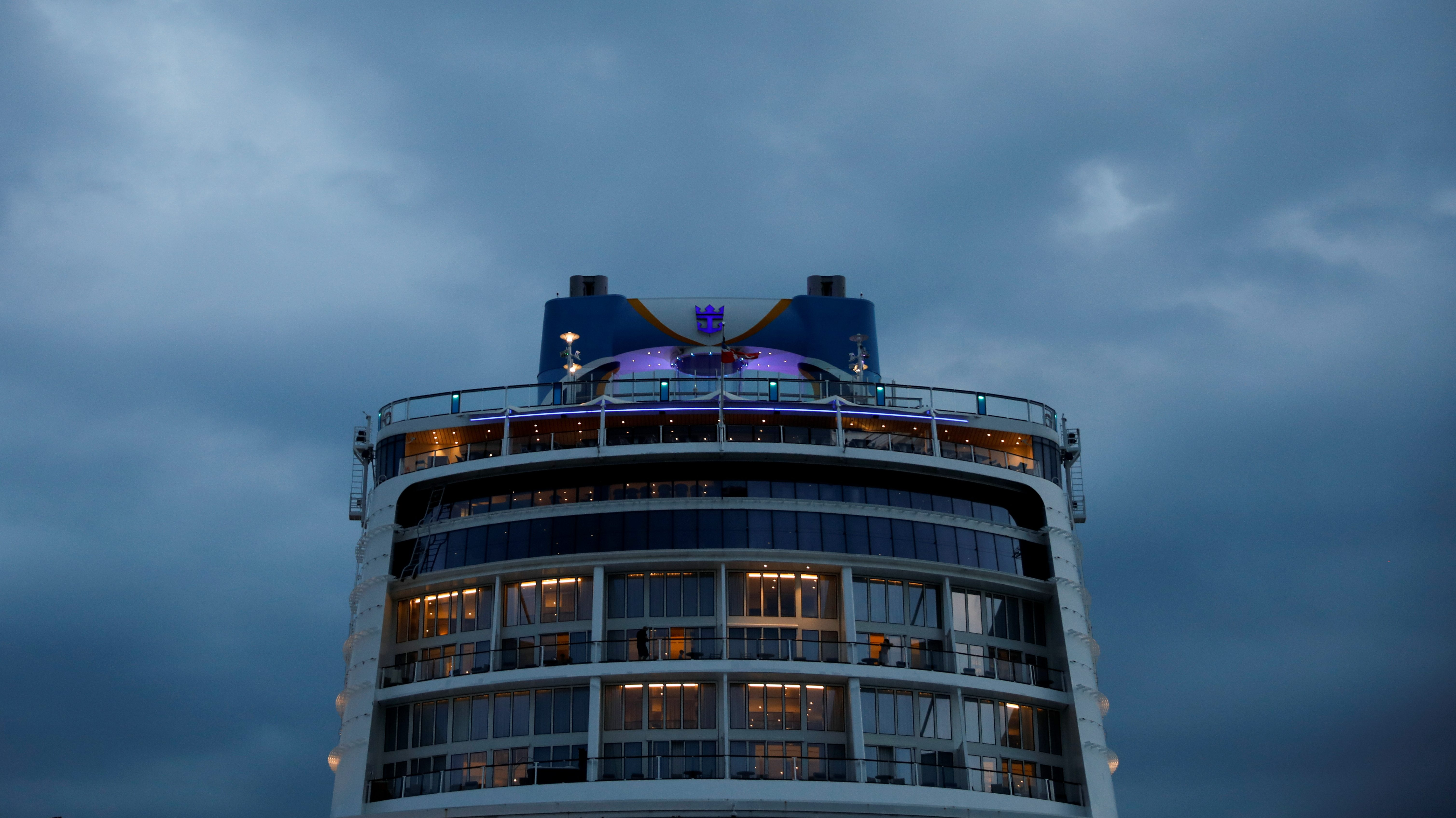 """The rear cabins of a Royal Caribbean ship, the Quantum of the Seas, are shown in front of dark, cloudy skies during a """"cruise to nowhere"""" in Singapore."""