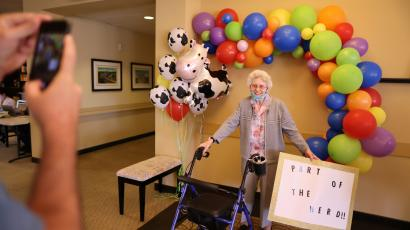 Marcie Meek, 88, poses for a photo with a sign referring to herd immunity after receiving the coronavirus disease (COVID-19) vaccine at the Brightwater Senior Living community in Highland