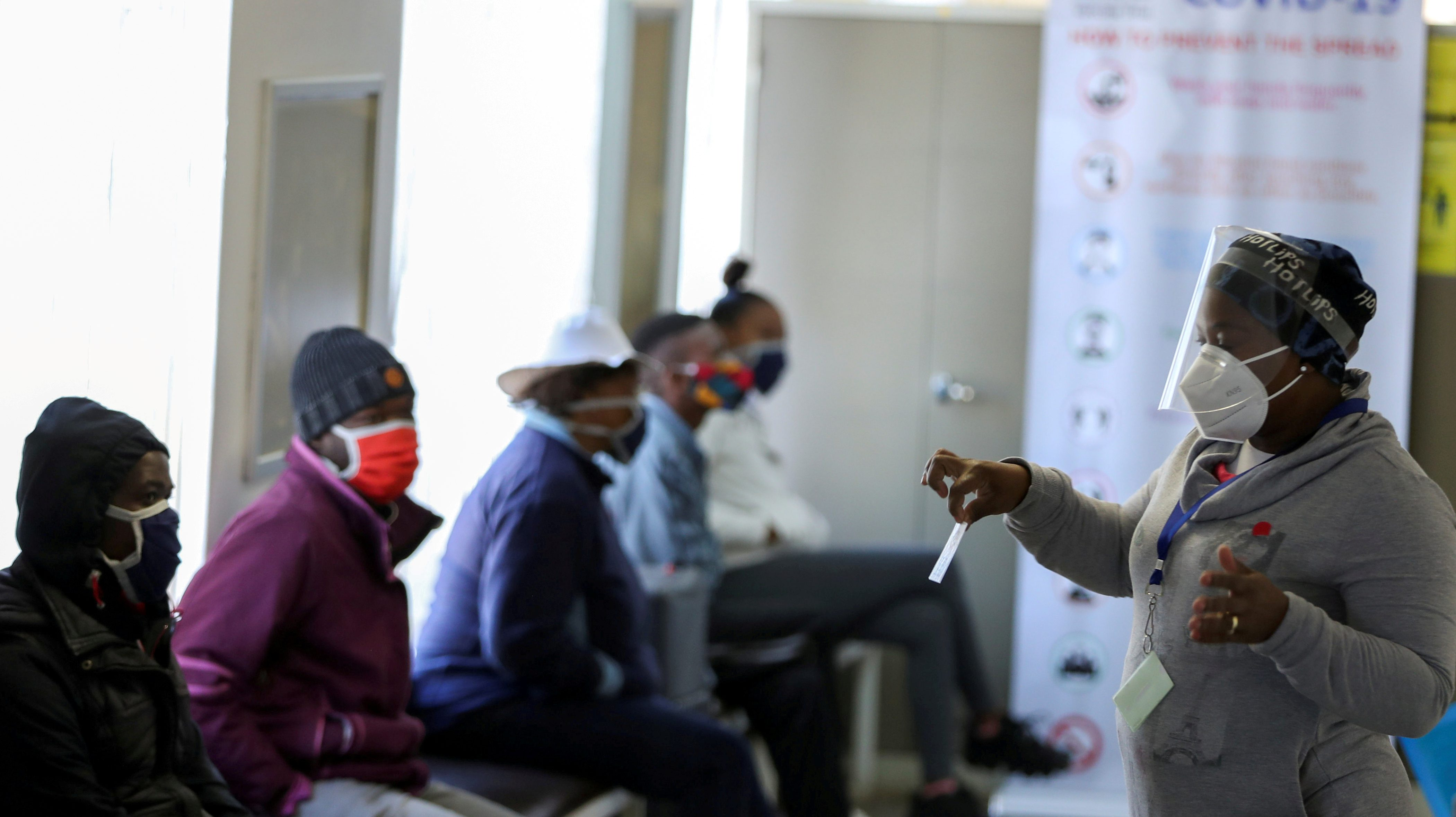 A medical worker talks to volunteers as they wait to receive an injection during the country's first human clinical trial for a potential vaccine against the novel coronavirus, at the Baragwanath hospital in South Africa, June 2020.