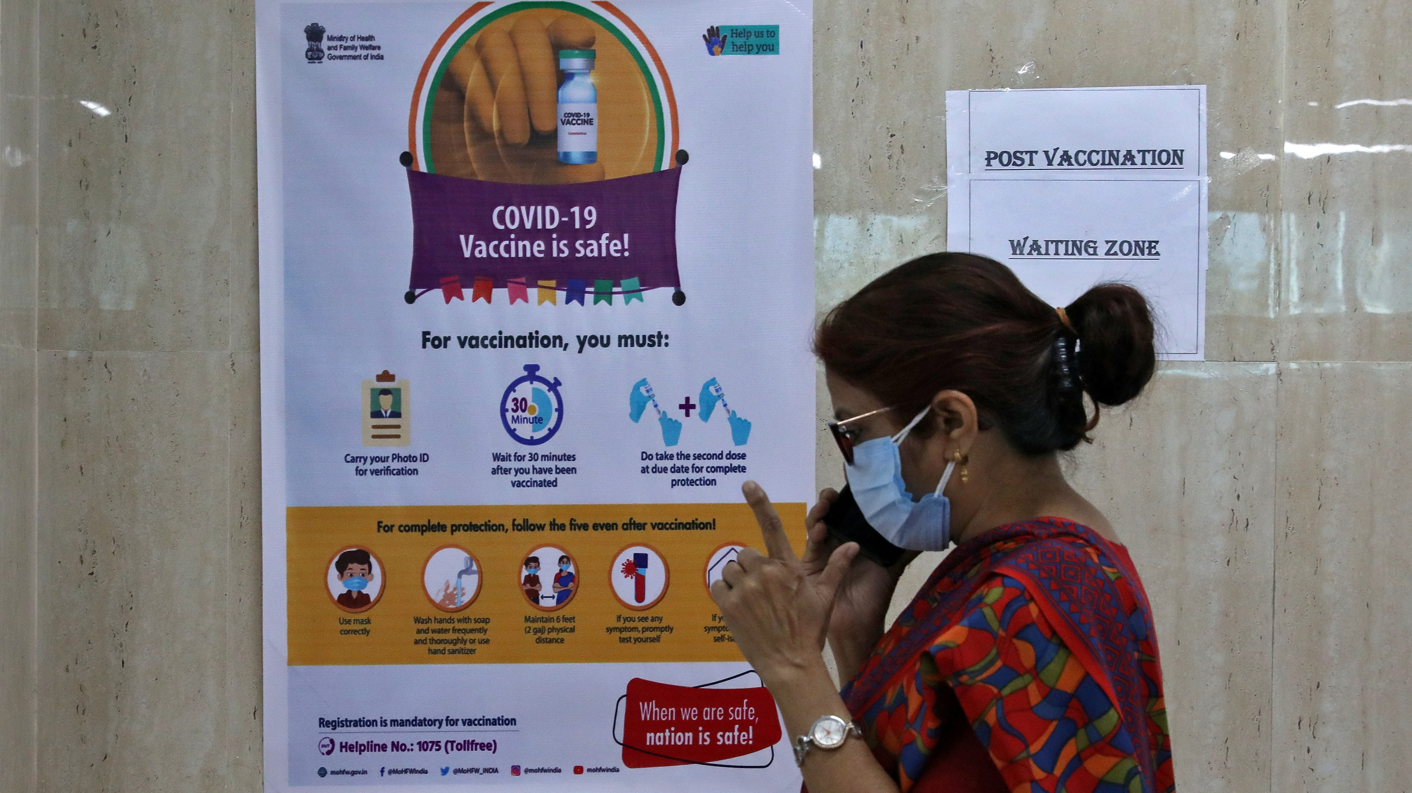 FILE PHOTO: A woman speaks inside a waiting zone area at a health clinic where COVID-19 vaccination is being given to healthcare workers in Kolkata