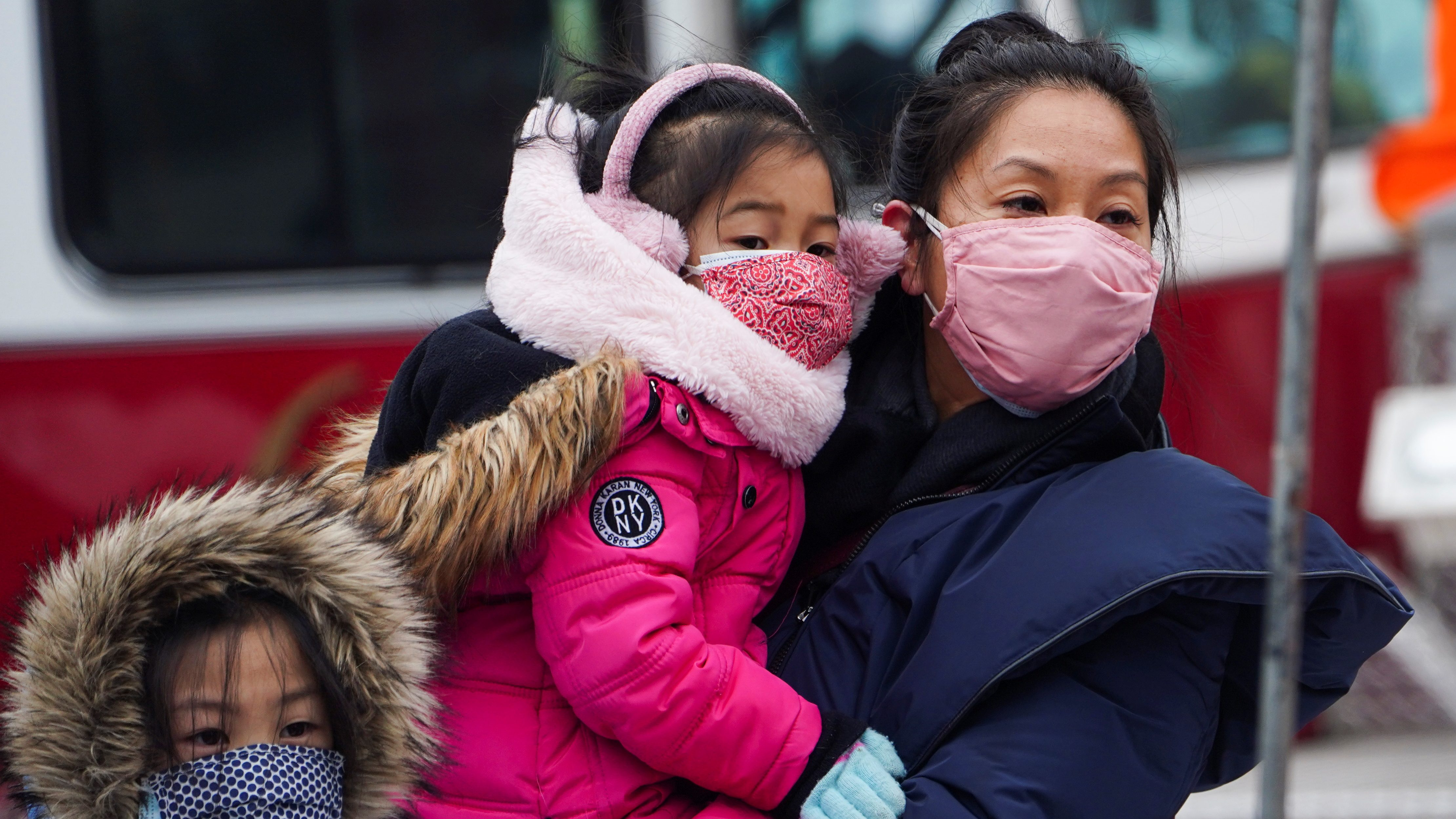 An Asian mother, wearing a light pink face mask and a dark blue winter coat, carries a young girl wearing a bright pink coat, pink earmuffs and a pink patterned facemask while standing next to an older young girl wearing a blue facemask. All three are watching Lunar New Year celebrations in New York City.