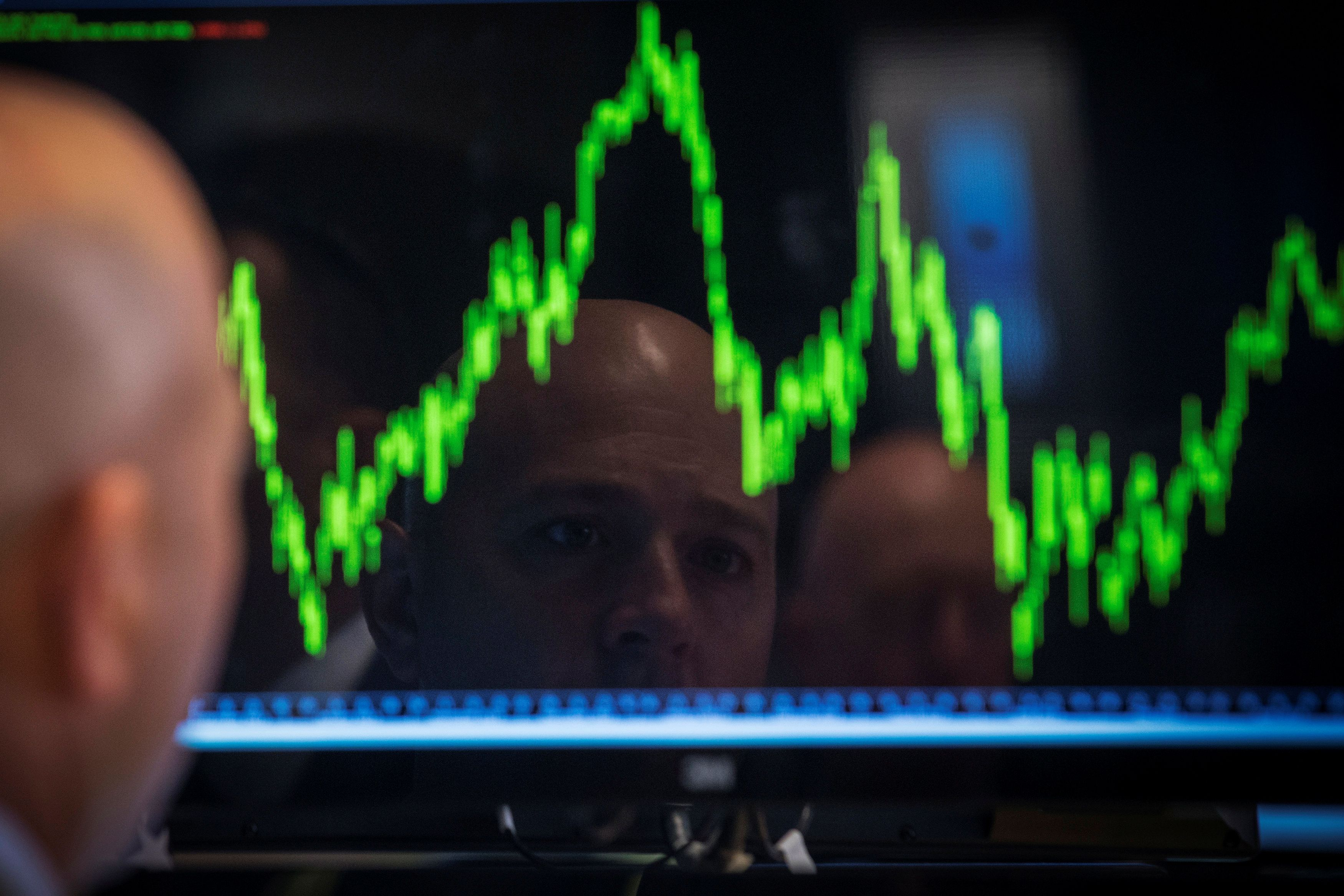 A bald man looks at a screen showing a volatile stock chart on the floor of the New York Stock exchange.