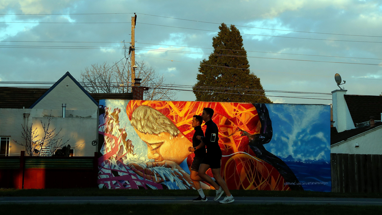 Men jog along a path in front of a mural in Berkeley