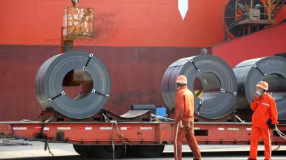 Workers load steel products for export to a cargo ship at a port in China