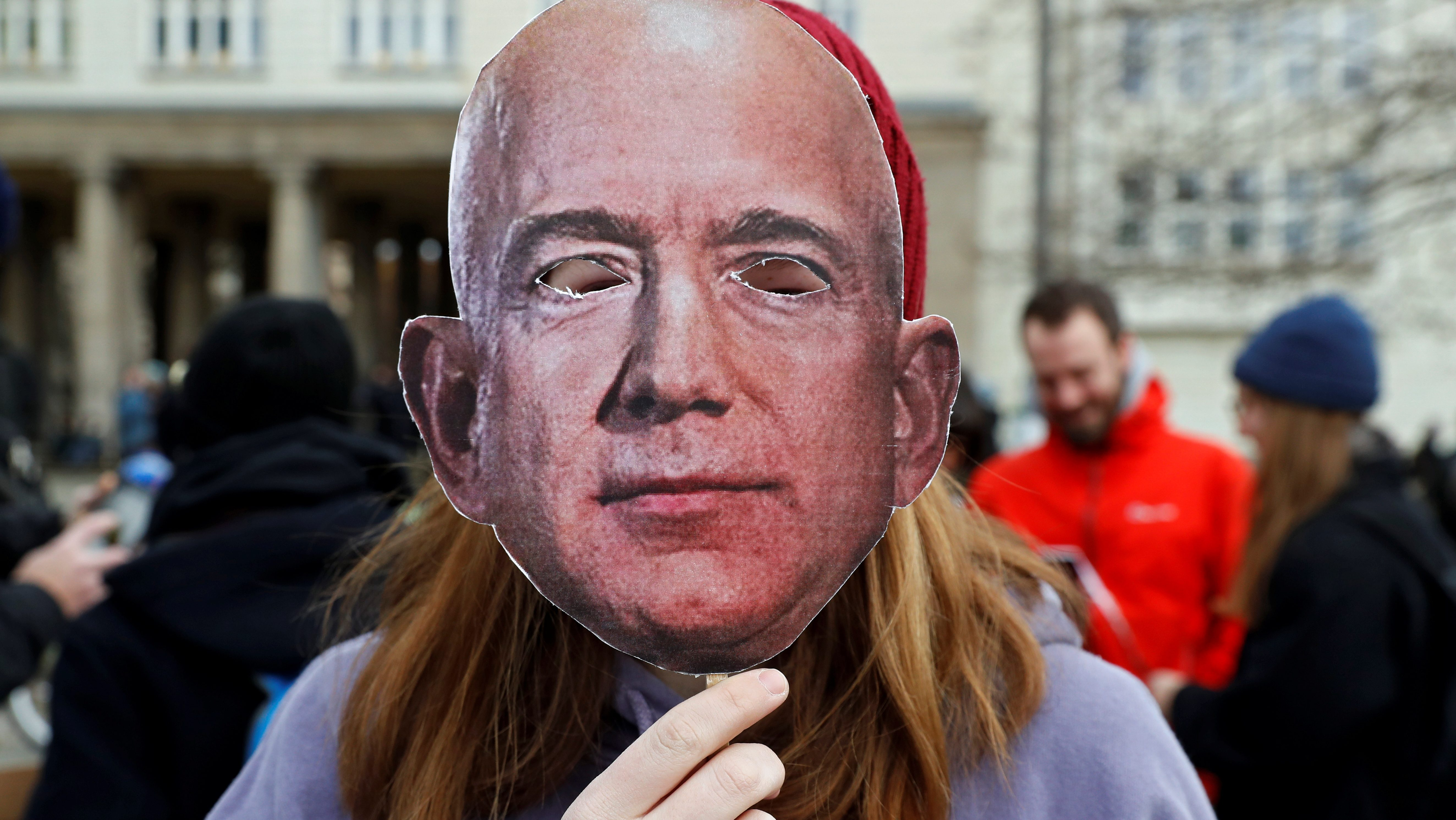 A woman holds up a mask depicting Amazon founder Jeff Bezos, during a protest against the opening of a new Amazon office