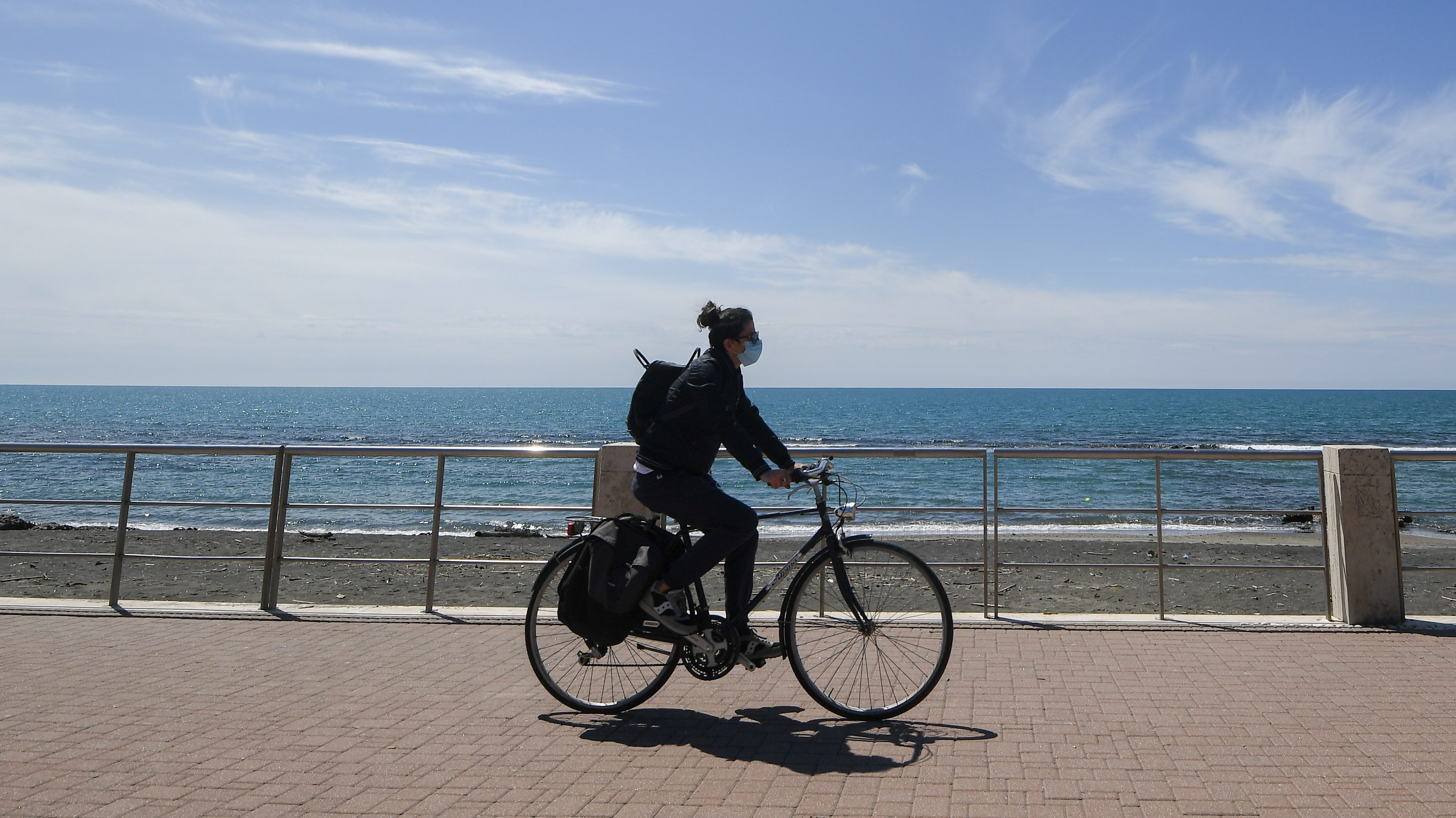 A woman with a face mask rides her bicycle at the touristic port in Ostia near Rome, as the spread of the coronavirus disease (COVID-19) continues in Italy, April 26, 2020