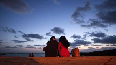 A couple sits along the seafront promenade at dusk in Mumbai's suburbs