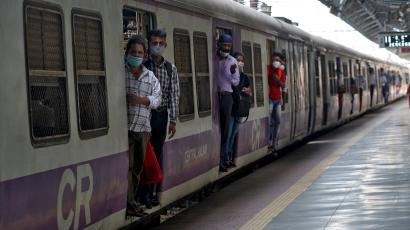 Commuters wearing protective face masks travel in a suburban train in Mumbai