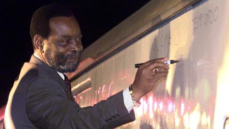 """South Africa's Zulu King Goodwill Zwelithini signs a message on a train carriage in Zulu, """"Phambili Ngemfundo"""" or """"forward with education"""" at Durban station in 2000."""