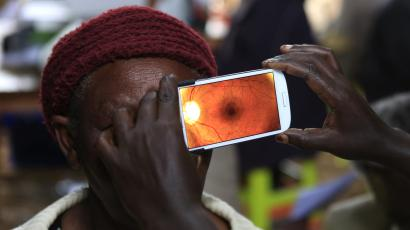 A woman undergoes an eye examination using a smartphone.