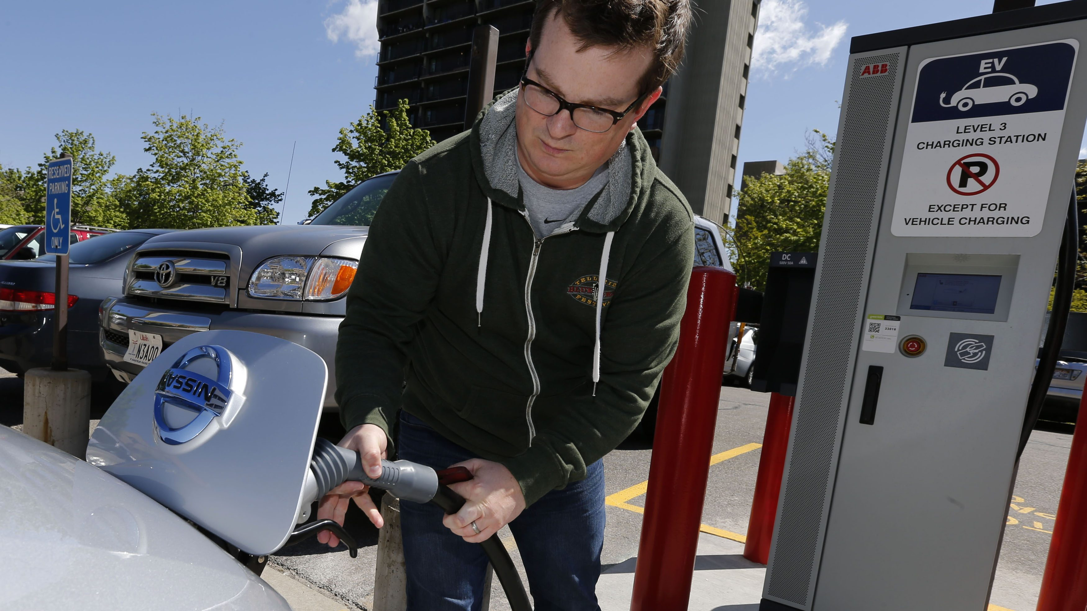 A man hooks up a charging cable so he can charge his 2013 Nissan Leaf electric car at ABB Inc.'s DC fast charging station in Salt Lake City