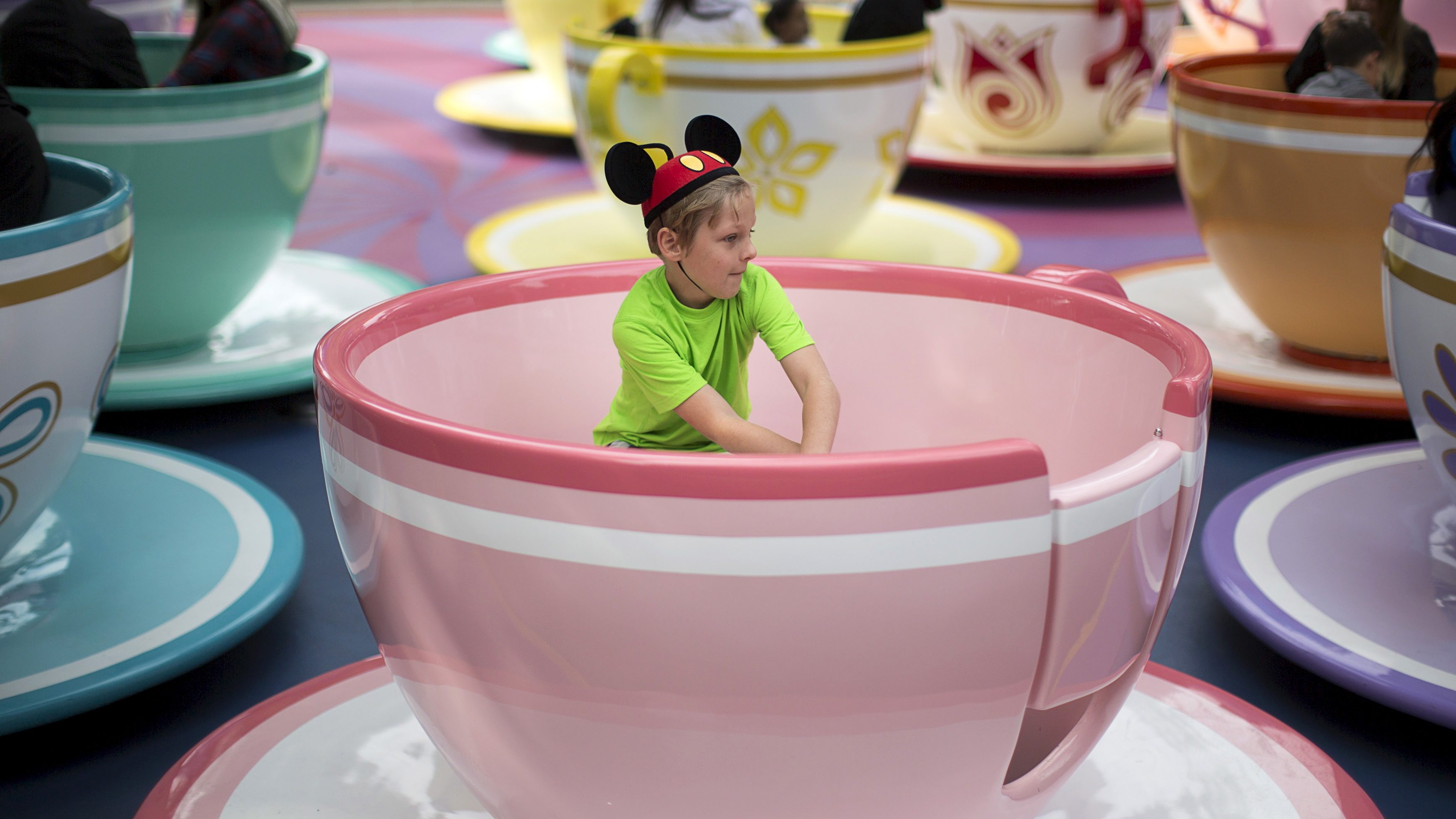 A young boy wearing a Mickey ears hat and a lime green t-shirt sits in the middle of a large tea cup and saucer on the Tea Party ride in this file photo of the Disneyland theme park in California.