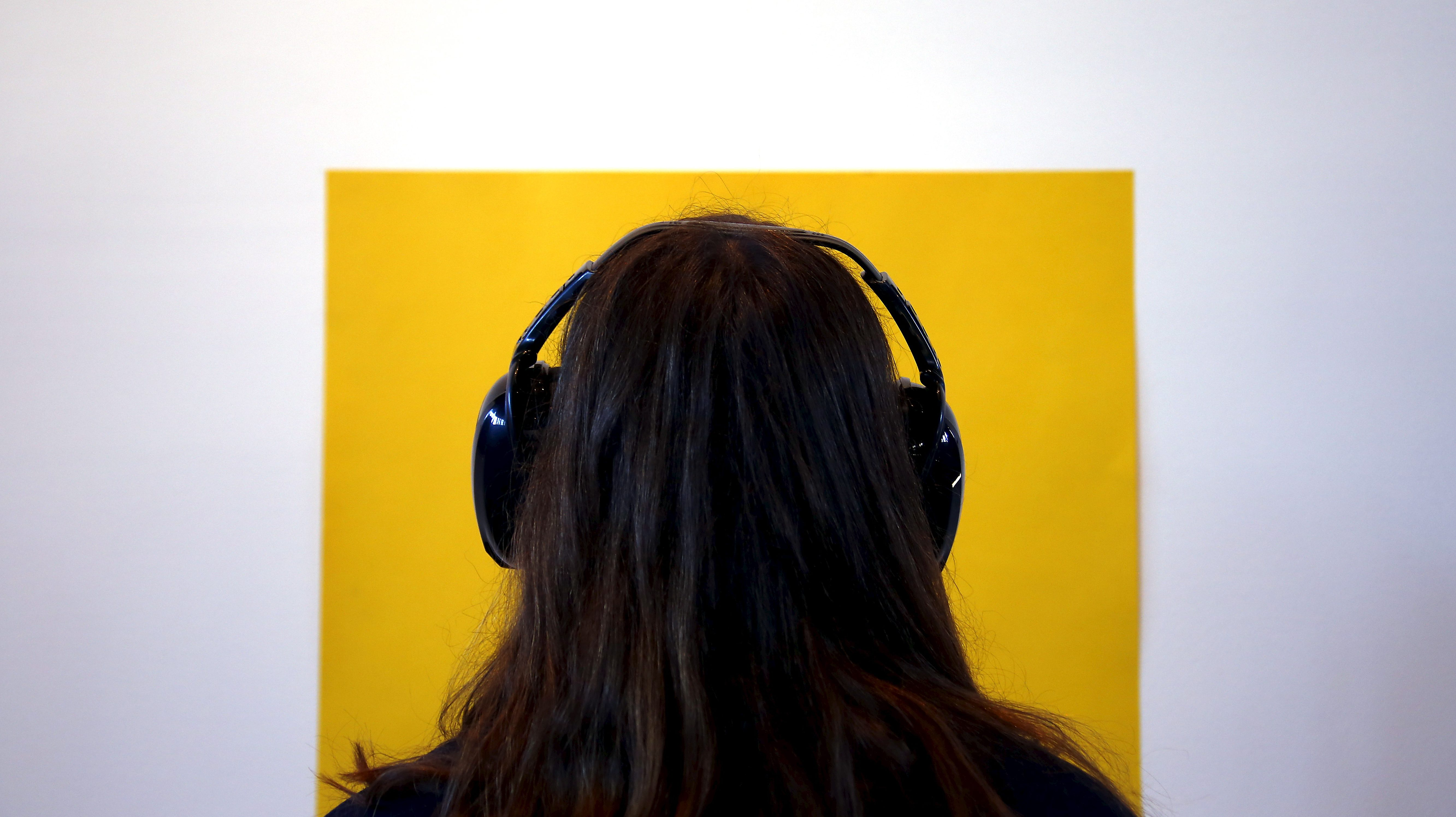 Photo of a female wearing headphones looking at a yellow square