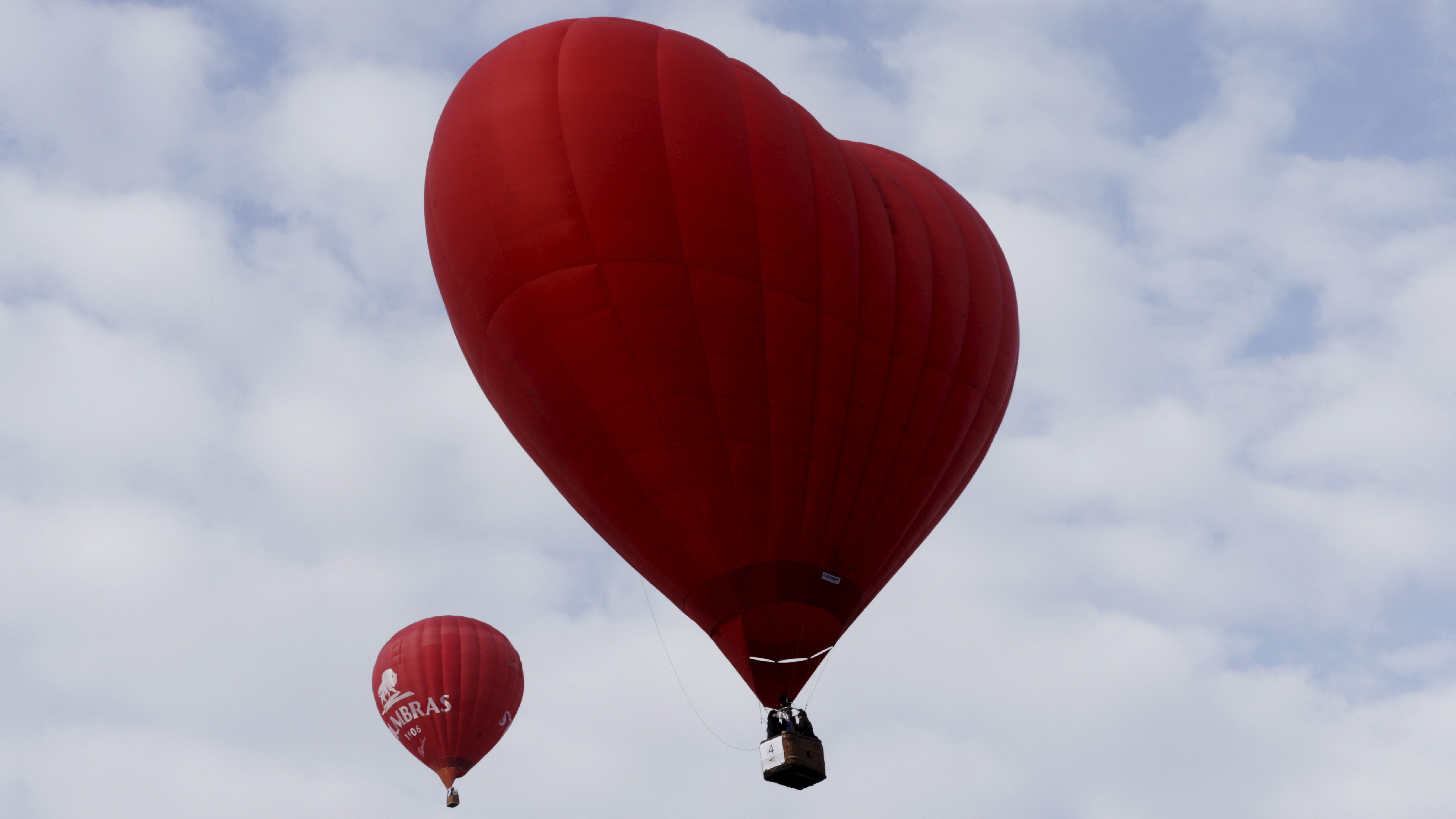 A giant red heart balloon floats in the air