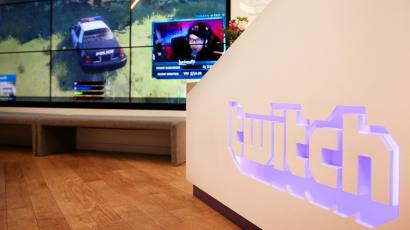 A wall of video monitors with real-time video game play is seen at in an office, next to a wall displaying the Twitch logo.