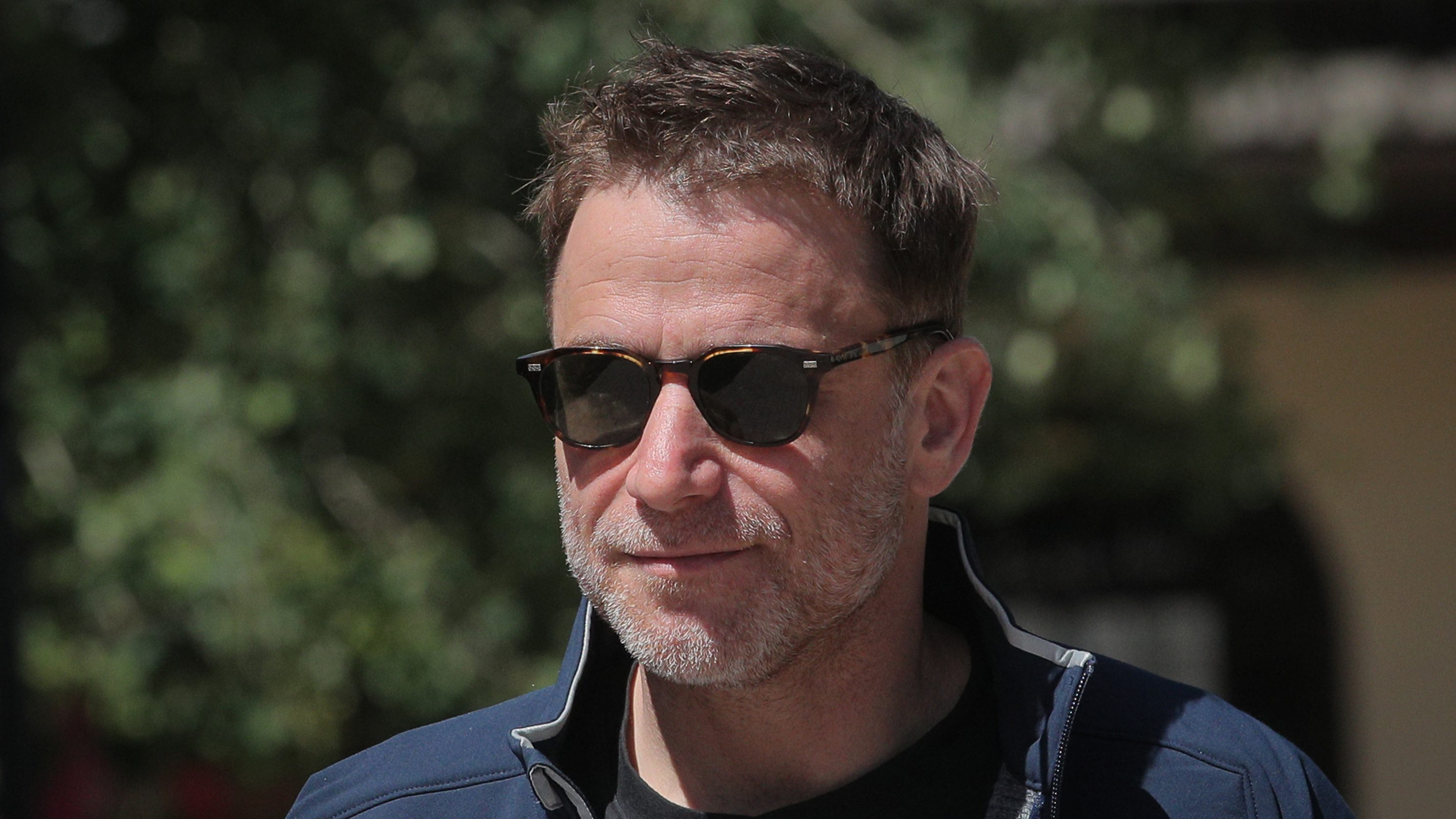 Stewart Butterfield wears sporty sunglasses and generally looks unconcerned.