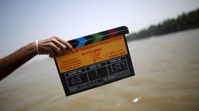 Member of a film crew holds a clapper board during the shooting of Bollywood film 'Black Home' at a beach on the outskirts of Mumbai