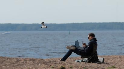 A person sitting on a beach with their laptop and computer.