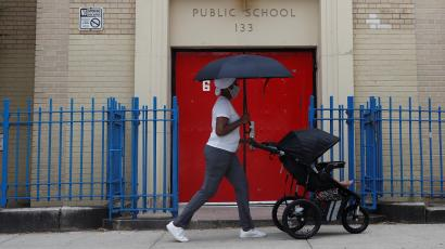 A woman pushes a baby in a cart past the entrance to Public School 133 in New York City