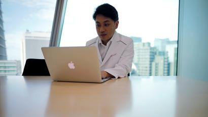 A doctor in a white lab coat sits in front of a laptop.