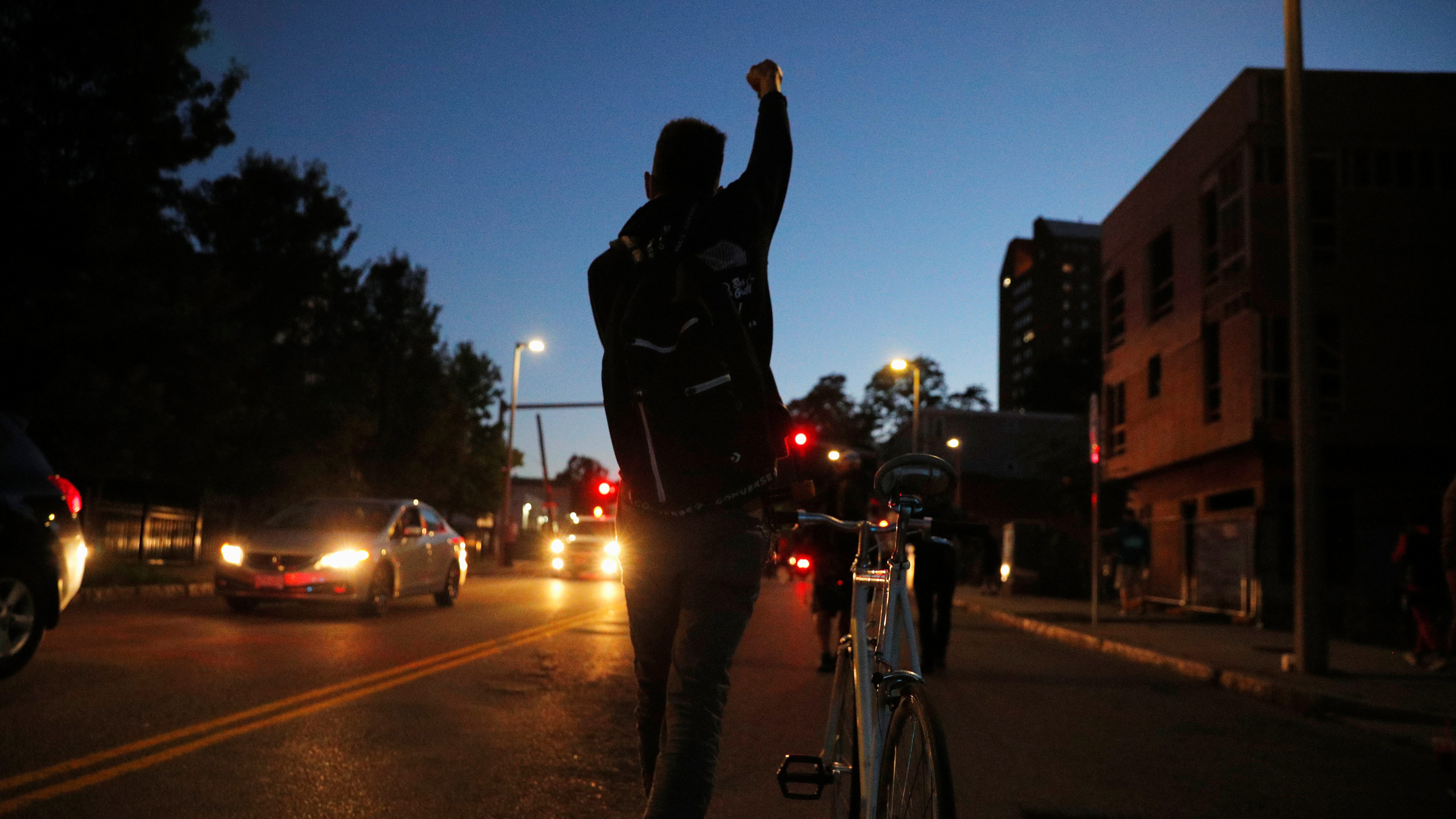 A cyclist gestures as demonstrators march during a rally against racial inequality and to call for justice a week after Black man Jacob Blake was shot several times by police in Kenosha, in Boston, Massachusetts, U.S., August 30, 2020.