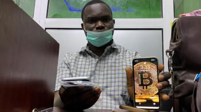 "Abolaji Odunjo, a gadget vendor who trades with bitcoin, poses with his mobile phone after an interview with Reuters at his store at the '""Computer village"", in Lagos"