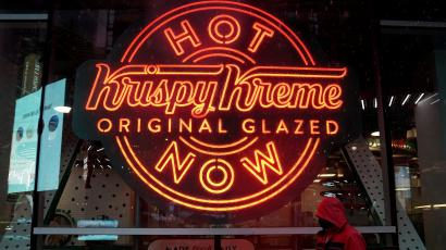"""A man walks past a Krispy Kreme """"Hot Now"""" neon sign in Times Square"""
