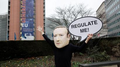 "An activist wearing a paper mache Mark Zuckerberg mask holds a sign that says ""Regulate me!"""