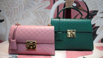 Two Gucci handbags are displayed in the window of a store