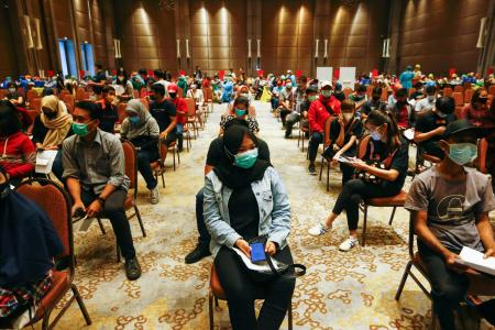 People wait to be vaccinated at a shopping mall in Tangerang, near Jakarta, Indonesia.