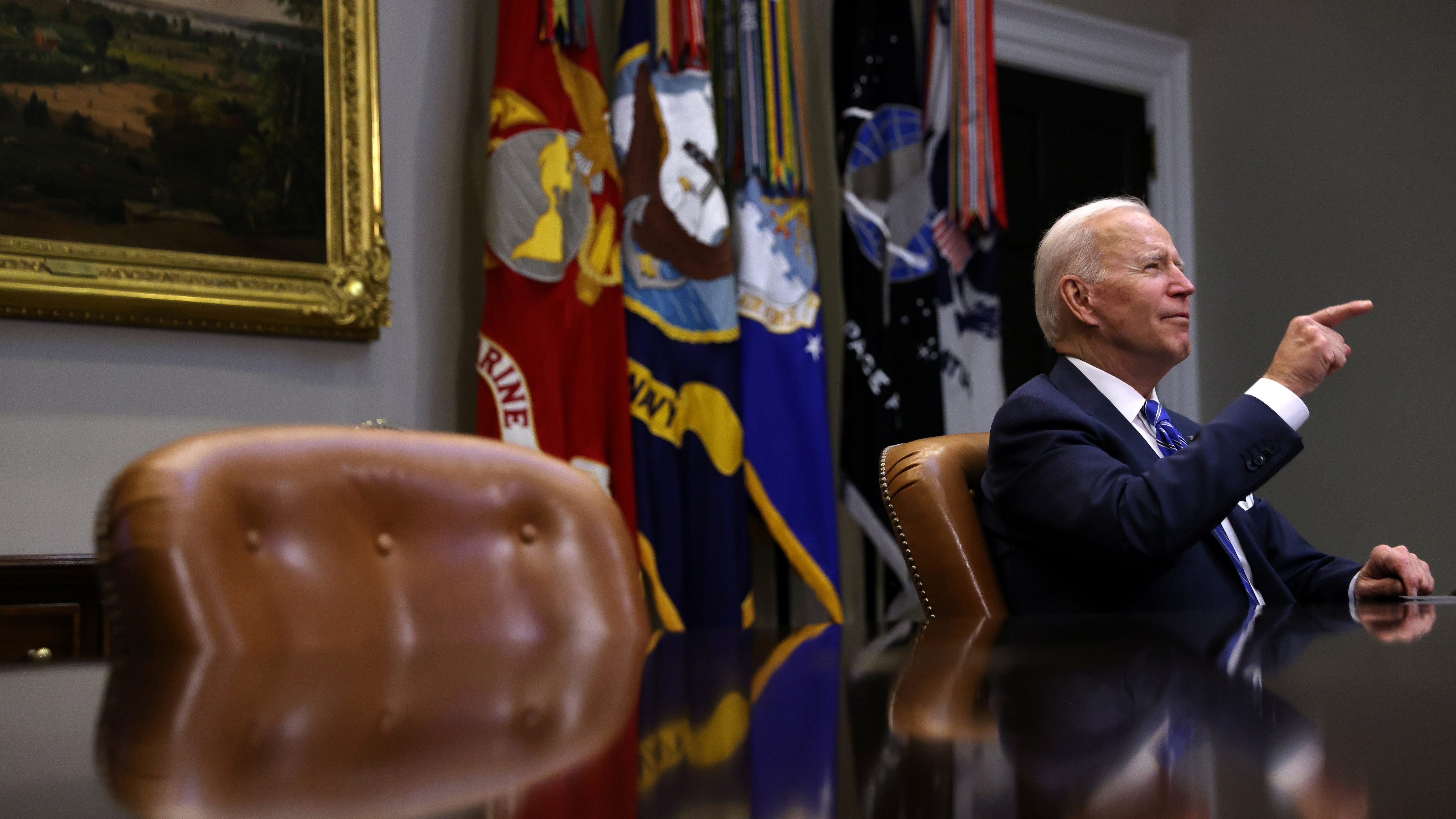 US president Joe Biden sits at a conference table and points.
