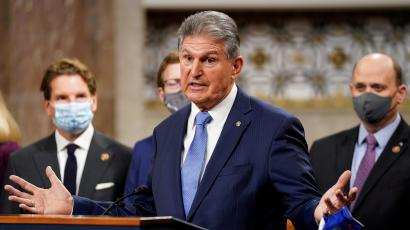 Joe Manchin spreads his arms wide while addressing reporters at the Capitol.