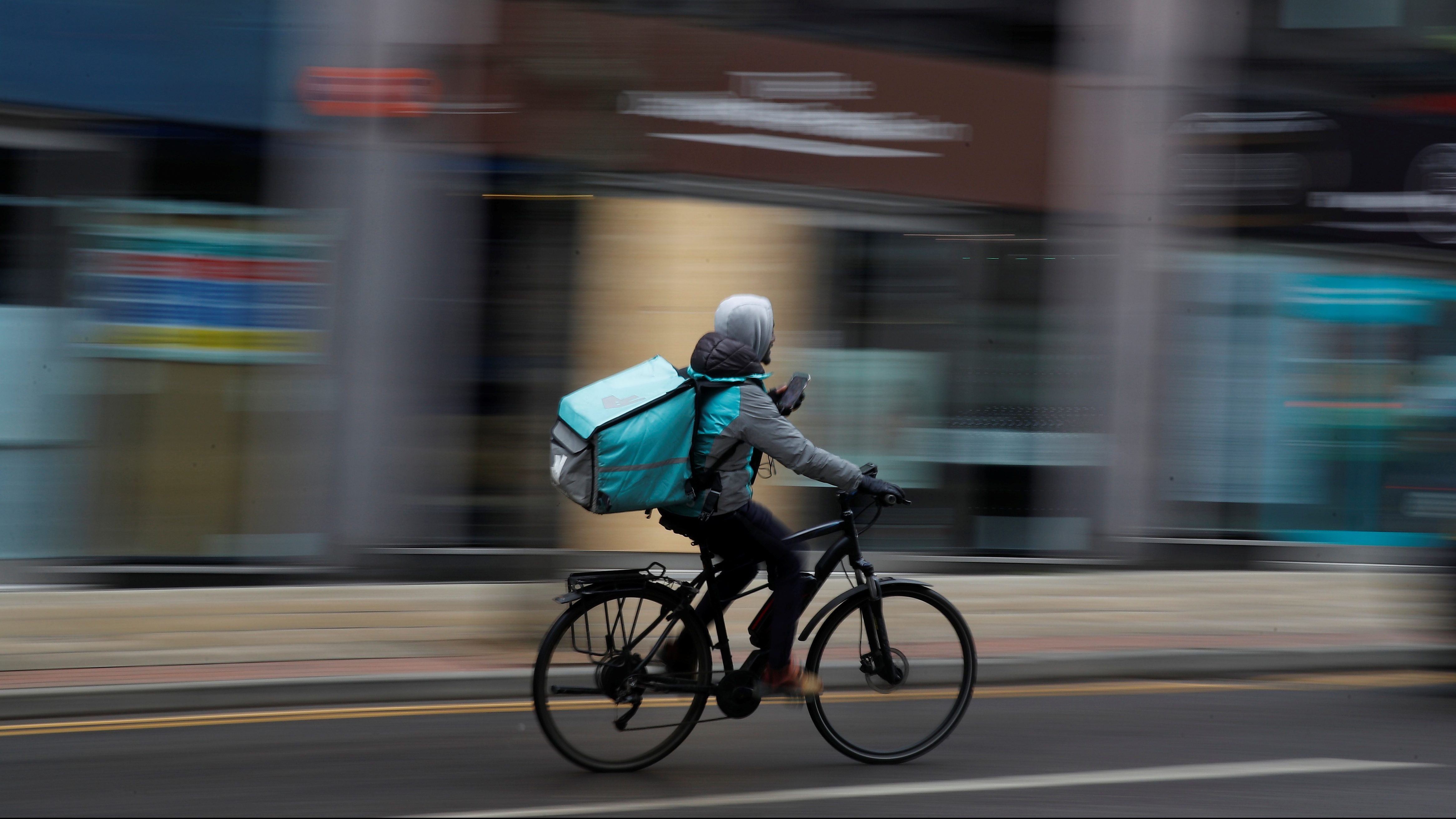 A deliveroo delivery driver cycles through the centre of Manchester