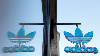 The Adidas logo is mirrored in the window of one of its stores in Germany