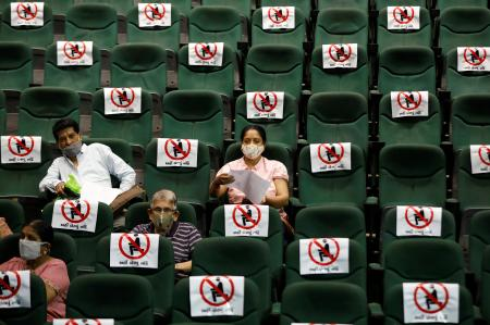 People wait after receiving their vaccine in a converted auditorium in Ahmedabad, India