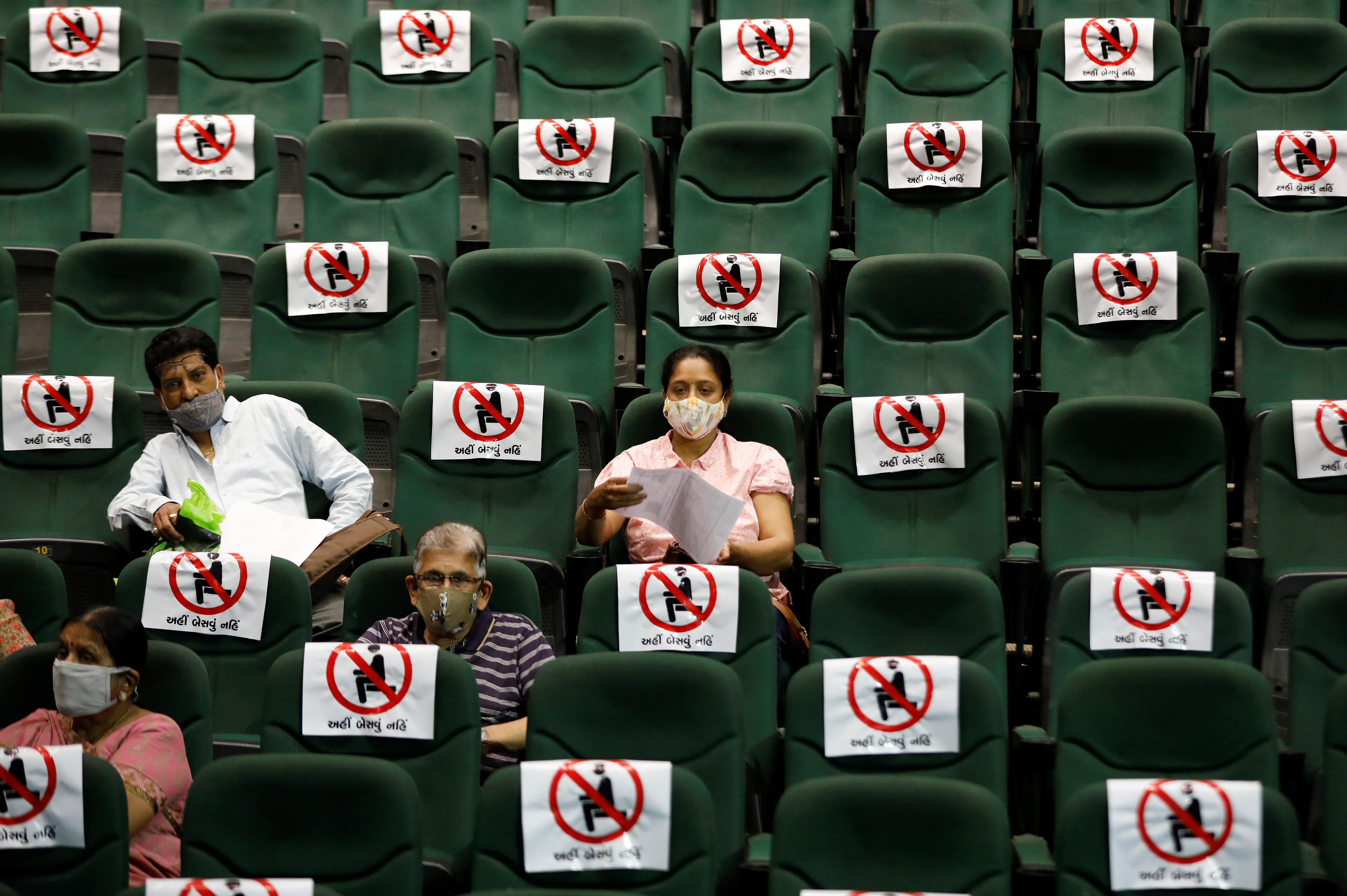 As pessoas esperam após receber a vacinação em um auditório reformado em Ahmedabad, Índia