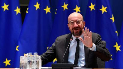 European Council President Charles Michel waves in front of an EU flag.
