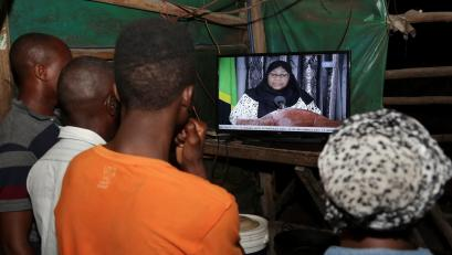 Residents watch the announcement of the death of Tanzania's president John Magufuli, addressed by vice president Samia Suluhu Hassan in Dar es Salaam, Tanzania.