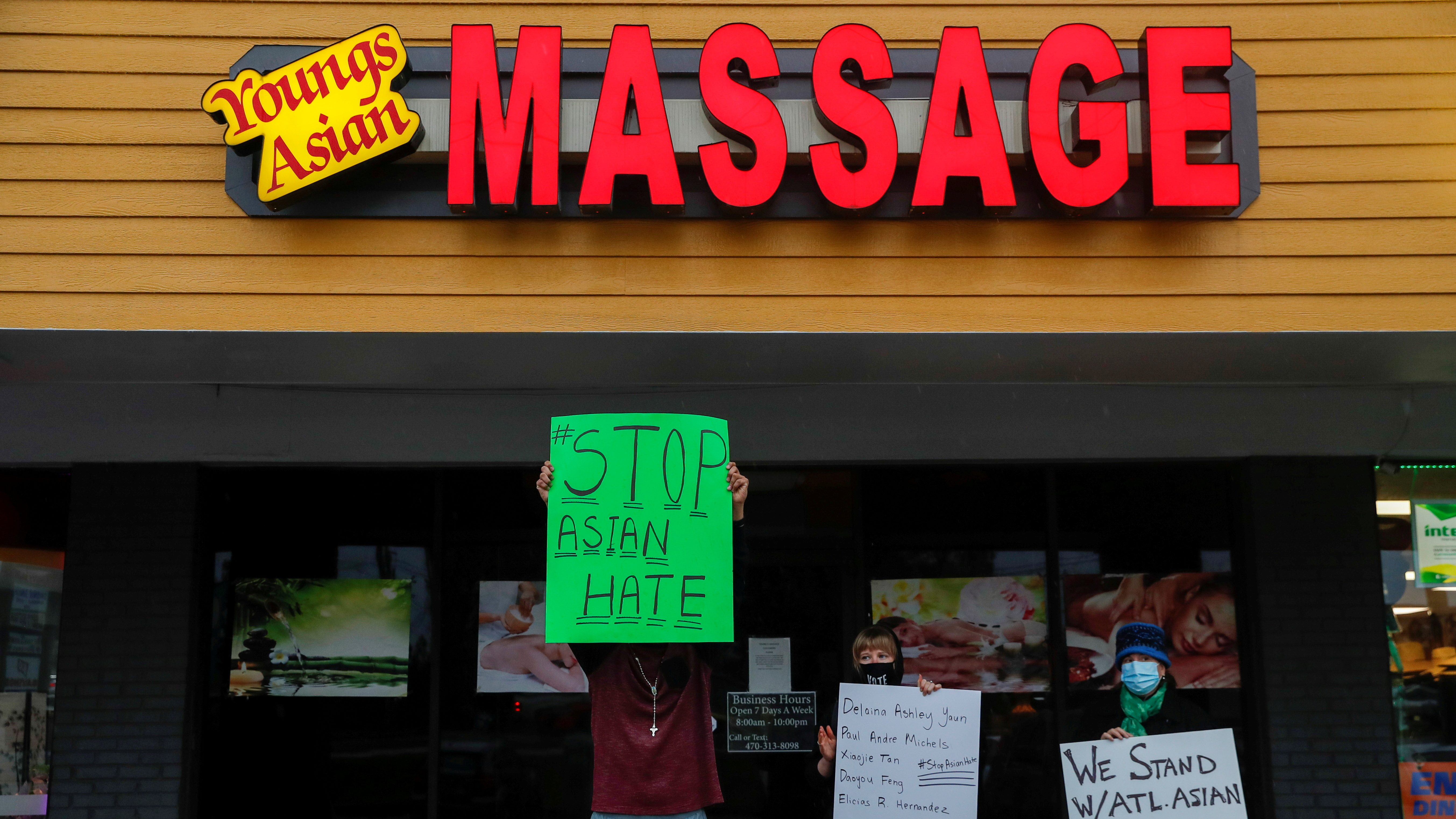 """A man holds a neon-green sign that says """"Stop the hate"""" in all-caps letters while wearing a red shirt, a gold chain, and blue pants in front of Youngs Asian Massage in Actworth, Georgia, after the location was one of three spas where a suspect shot and killed eight people. The word """"massage"""" is in large red letters and two other people are holding signs with the names of the victims and the words """"We stand with ATL Asian community."""""""