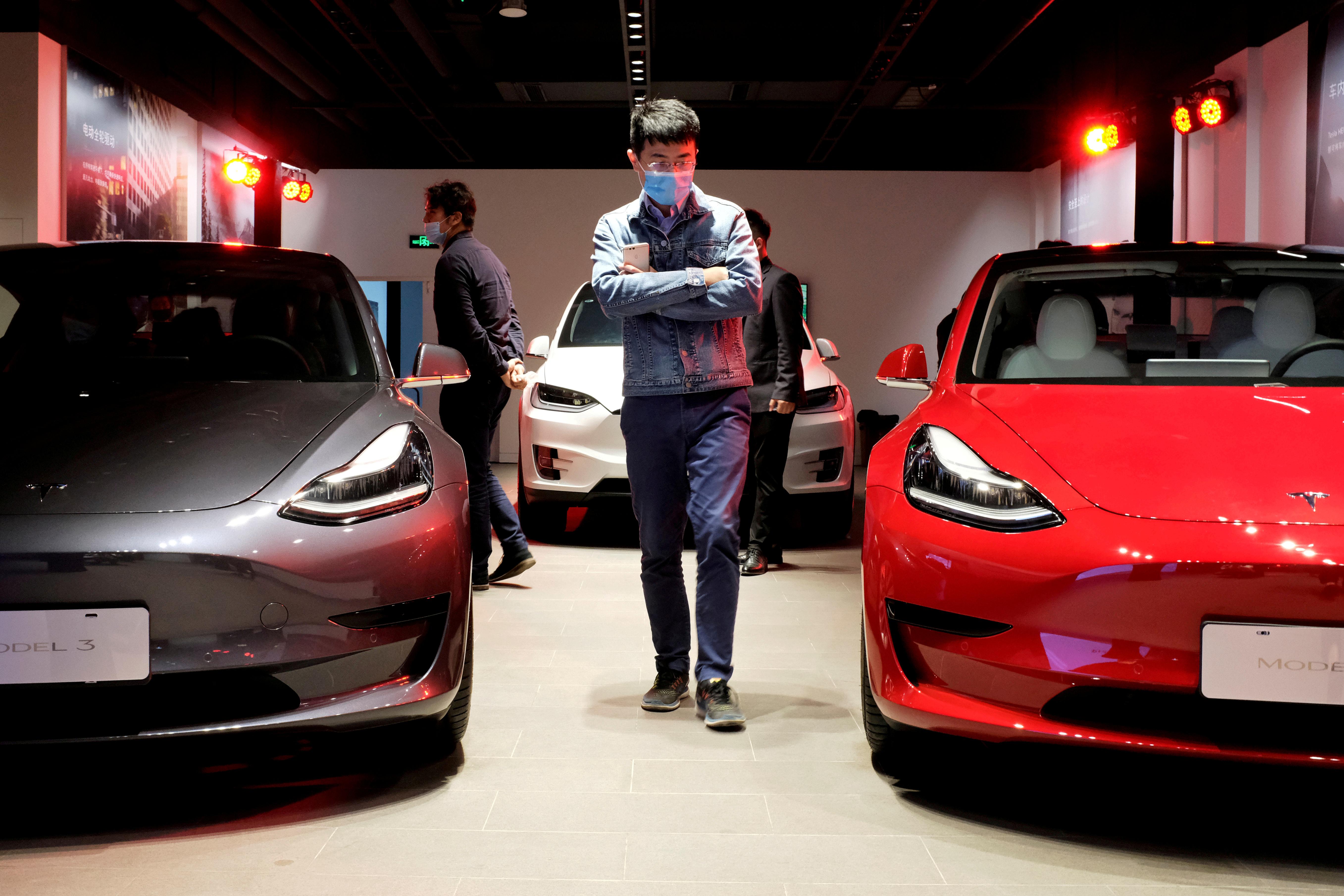 a man walks between two Tesla vehicles in the company's Shanghai showroom.