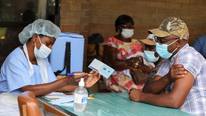A man receives a certificate after being vaccinated against the coronavirus disease (COVID-19) at Wilkins Hospital in Harare