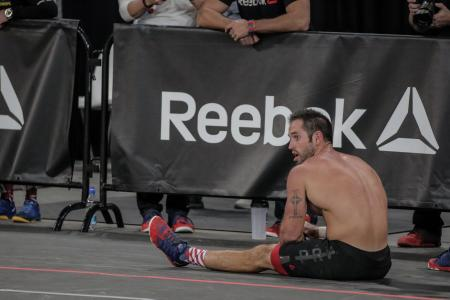 A CrossFit athlete takes a rest in front of a Reebok sign
