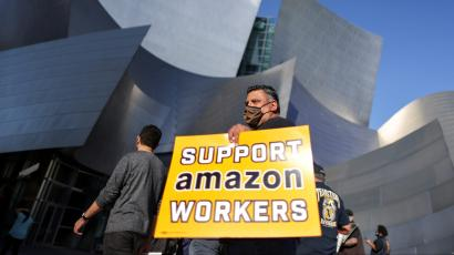 """A protestor holds a sign saying """"Support Amazon workers"""" in front of a building in Los Angeles"""