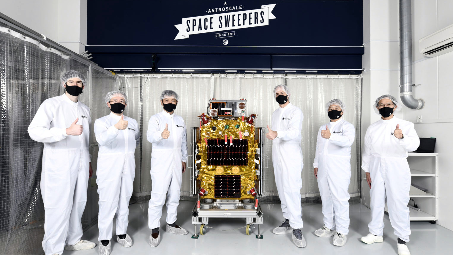 Astroscale execs pose with ELSA-d, the spacecraft that will validate their business.