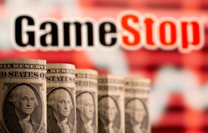 U.S. one dollar banknotes are seen in front of displayed GameStop logo