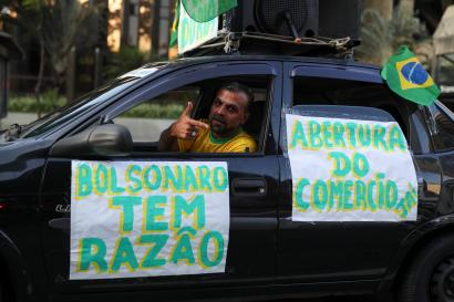 """A man gestures inside a car with banners reading """"Bolsonaro is right"""" and """"For the opening of the commerce"""" as supporters of far-right Brazilian President Jair Bolsonaro protest against the recommendations for social isolation of the Governor of Sao Paulo in April 2020"""