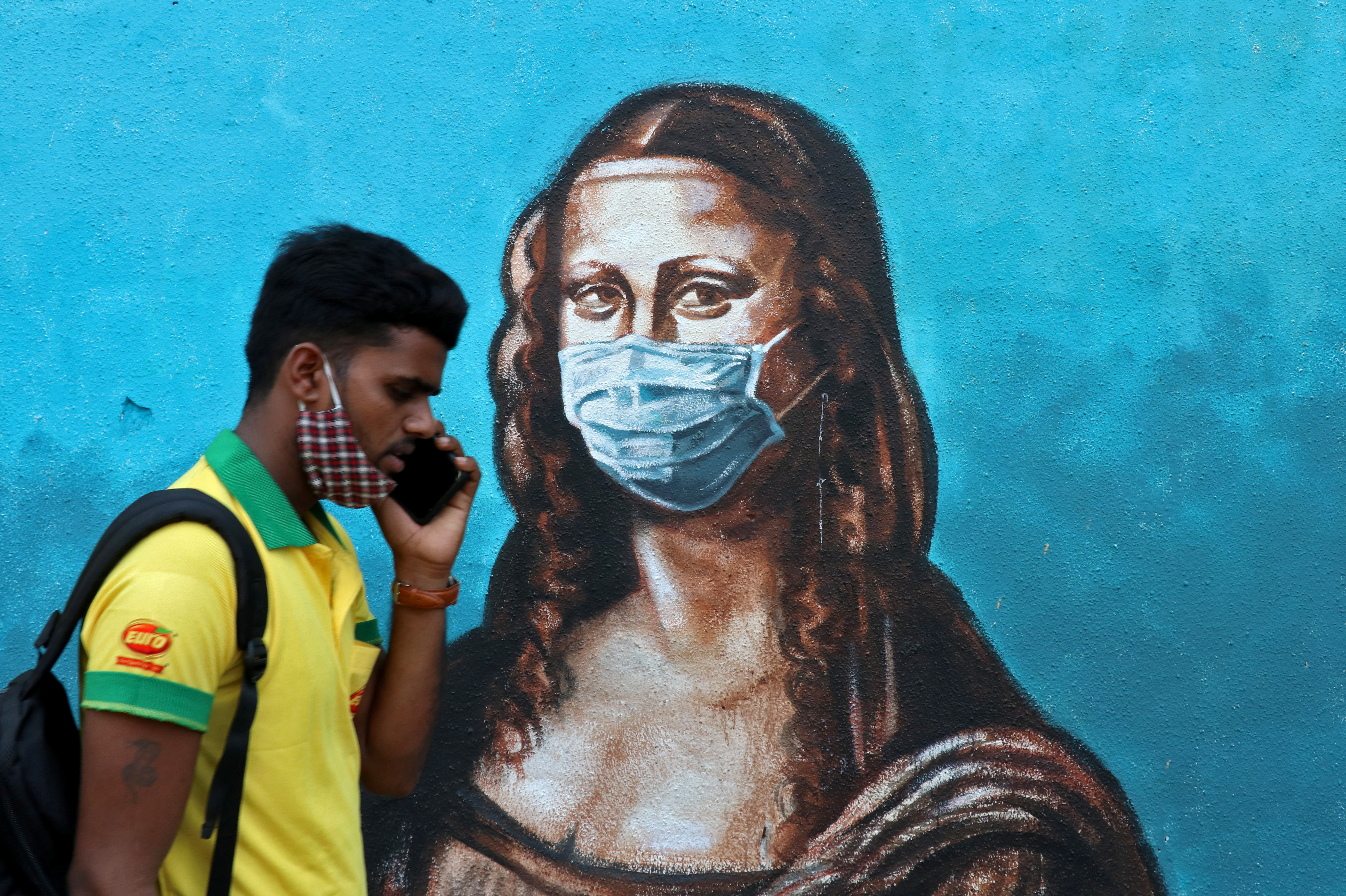 "A man walks past a mural depicting the ""Mona Lisa"" wearing a face mask amidst the spread of the coronavirus disease (COVID-19), in Mumbai"