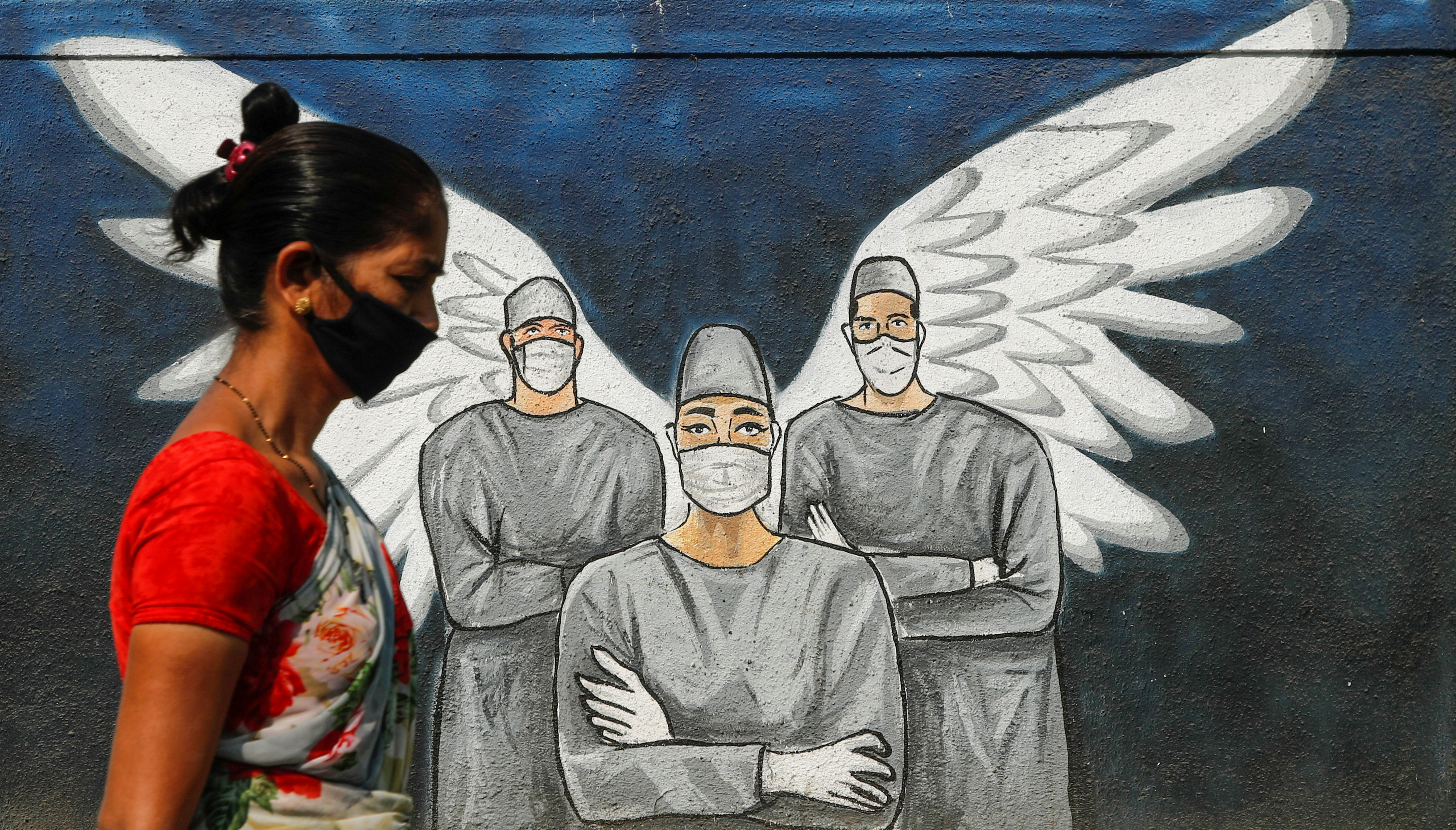 Woman wearing a protective mask walks past a graffiti amidst the spread of COVID-19, in Navi Mumbai