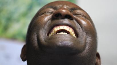 man leaning back his head and laughing